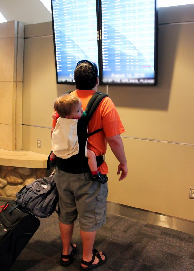 One of the best tips for flying with a baby is to take advantage of a baby carrier for keeping hands free in the airport.