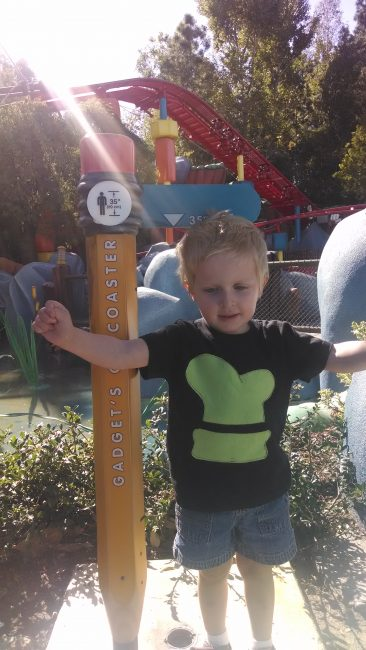 Child celebrates hitting a Disneyland Height Requirement