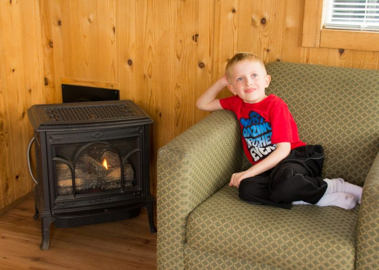 Child in cabin by fireplace