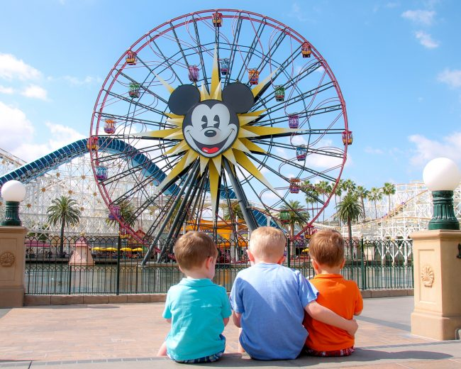 3 boys sitting at Disneyland photo spot in california adventure by mickey ferris wheel
