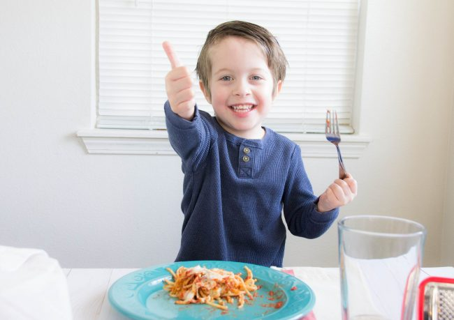 Kid giving thumbs up for trying new food