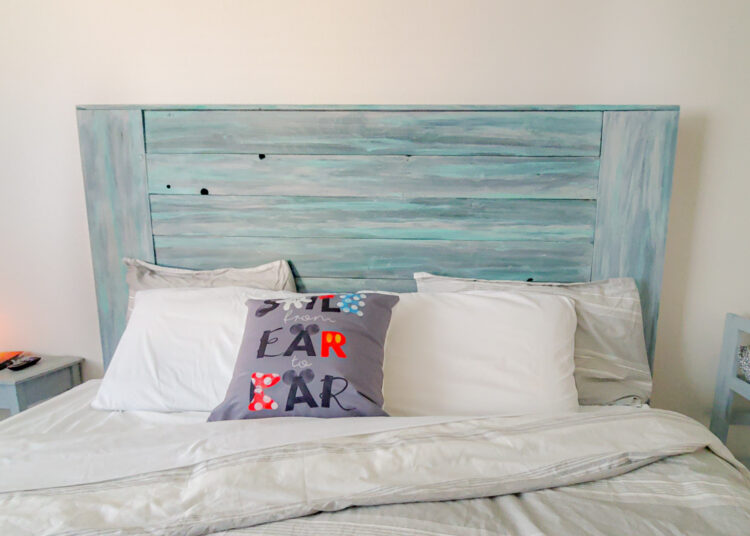 Rustic farmhouse headboard on king bed, distressed grays and teals to look like weathered wood