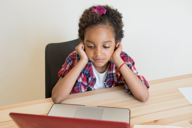 child at desk looking at laptop