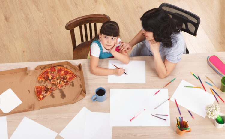 mom and child trying to work at dining room table with half eaten pizza near them