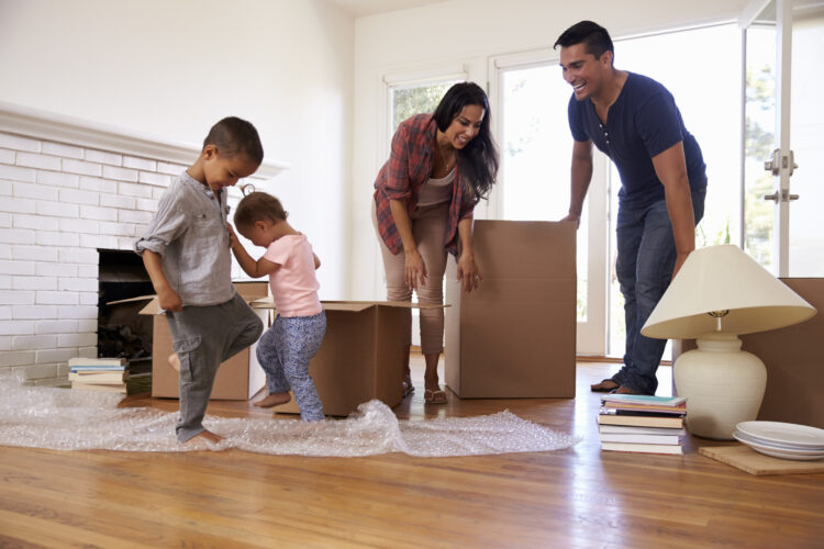 family dancing in living room near moving boxes