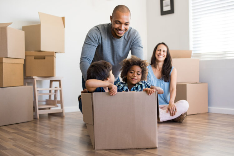 dad playing with kids in moving box, mom watching in background with boxes piled around her