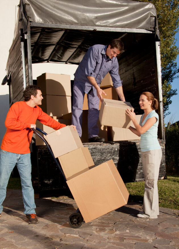 family unloading moving boxes with another adult helping