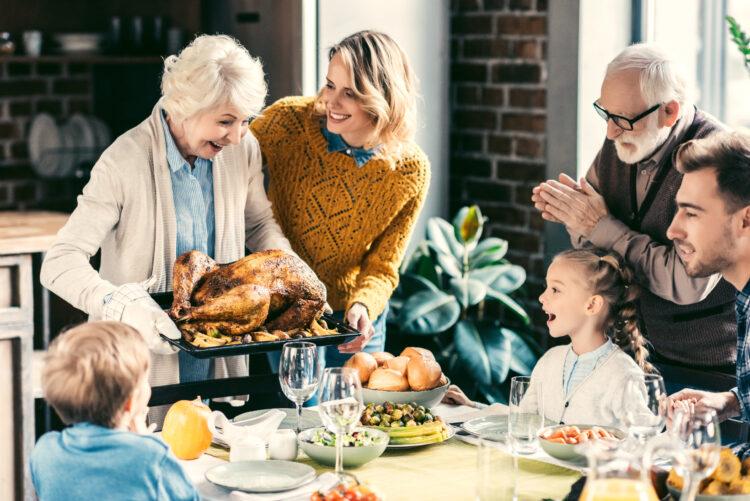 family having thanksgiving dinner, grandma bringing turkey to table
